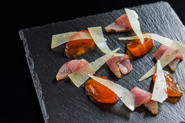 plate hamachi with Amaretto infused persimmons and shaved Manchego