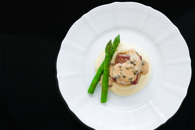 Plate the dish, by putting a layer of mashed potatoes down and then placing a piece of tuna on top.
