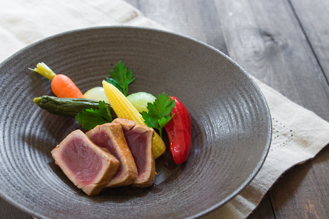 slice the tuna and plate with pickled vegetable and garnish