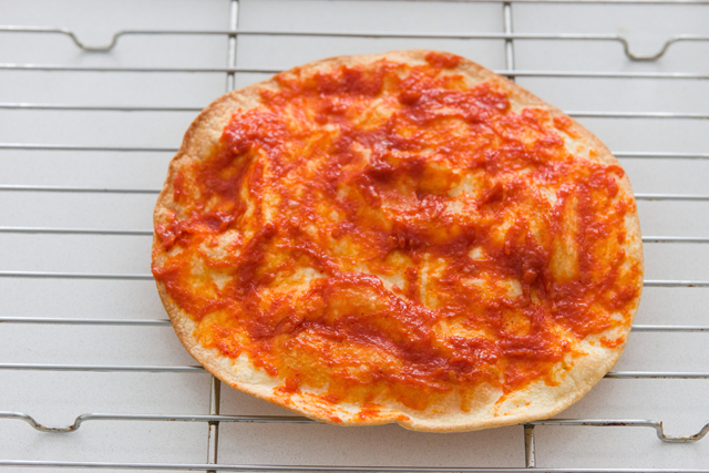 spread a thin even layer of the prepared pizza sauce onto each tortilla